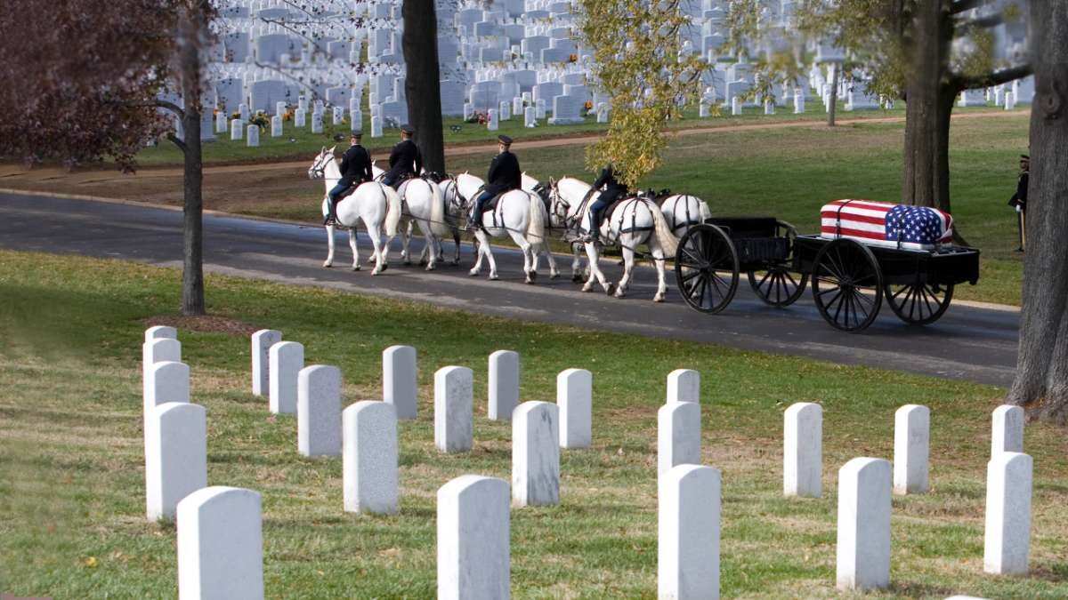 Horses pull casket through cemetery