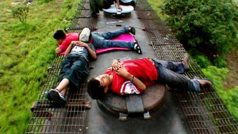 Kids sleeping on top of train car