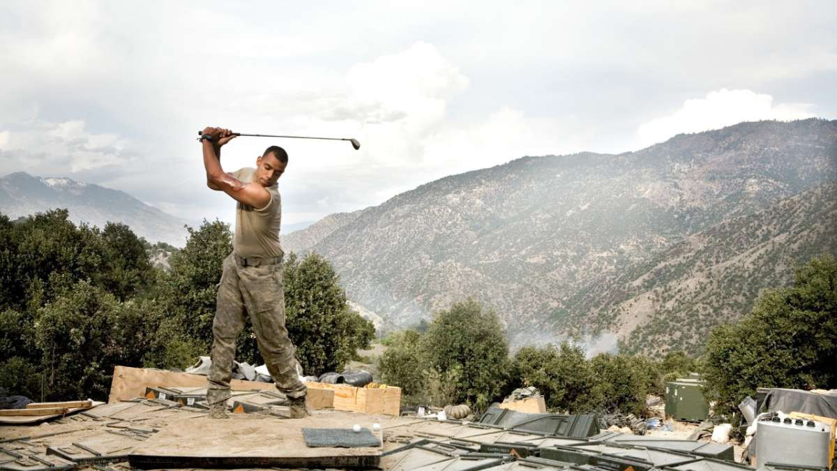 Soldier playing golf in rubble