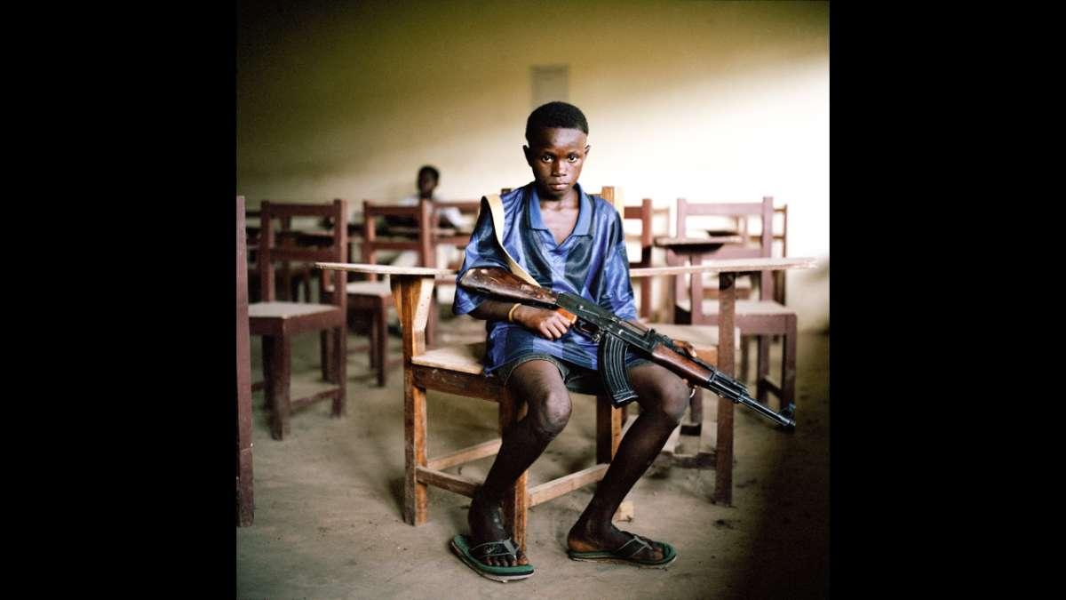Young boy in classroom with weapon