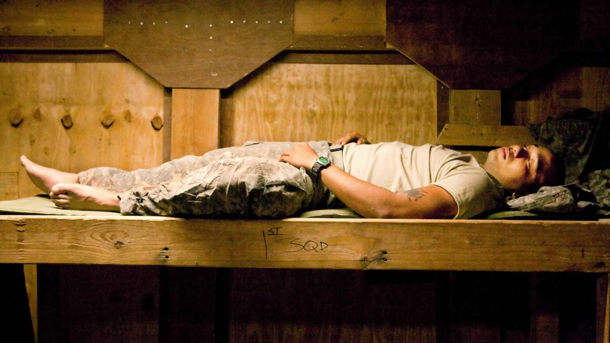 Soldier sleeping on wooden plank