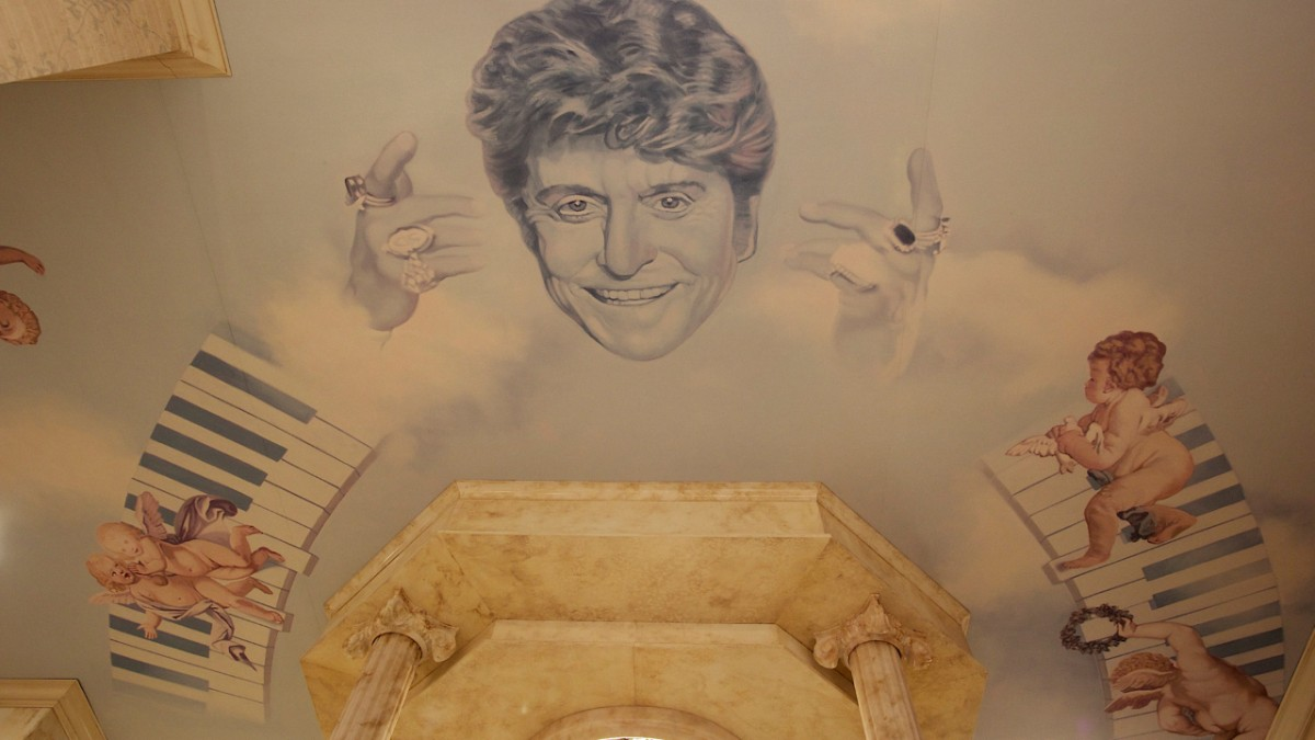 Portrait of Liberace on wall with angels