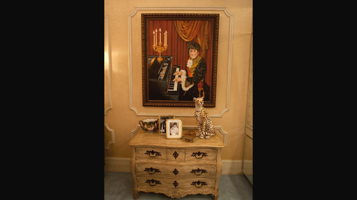 Liberace portrait over ornate chest of drawers