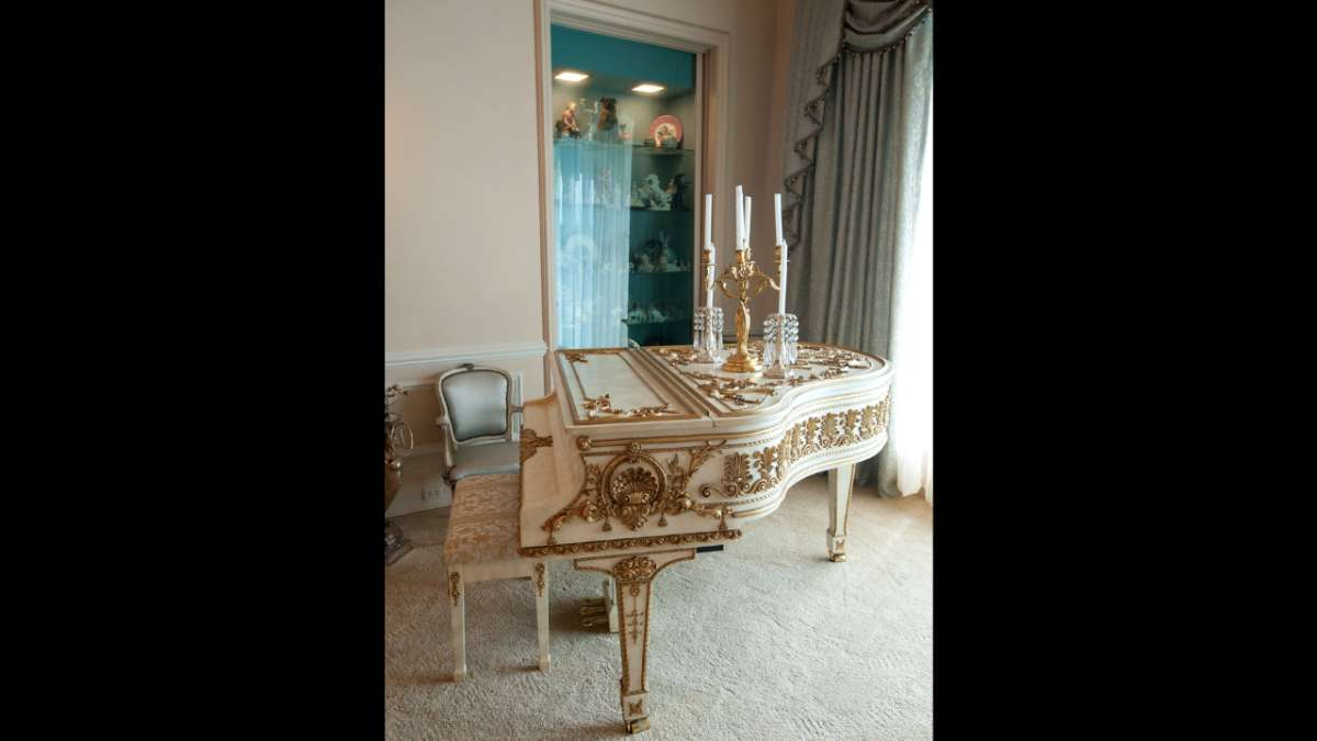Liberace gilt and white piano in home
