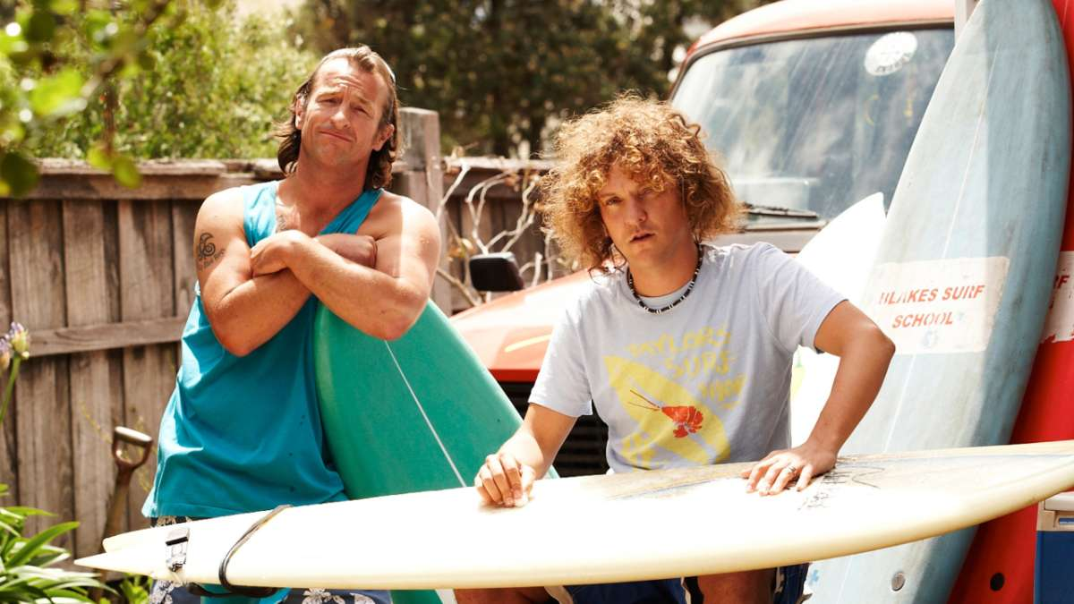 Blake waxing surfboard