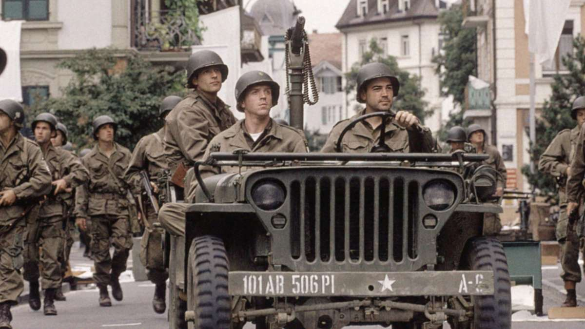 Three soldiers in jeep while others march