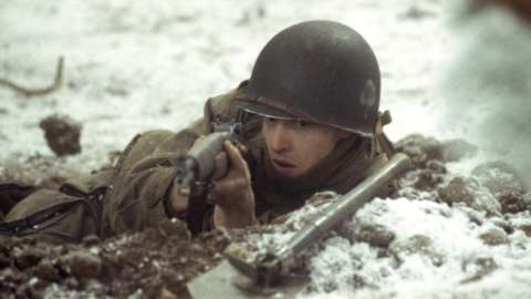 Soldier in foxhole aims rifle