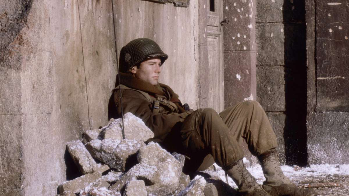 Soldier sits against wall in the snow