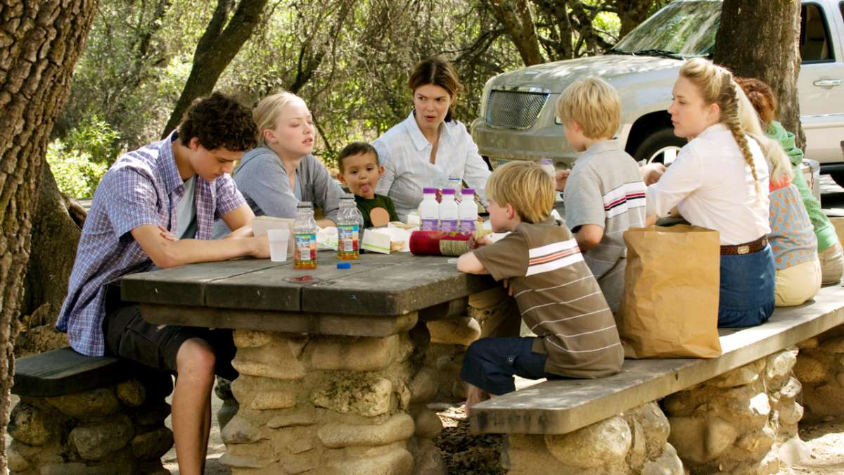 Henrickson family sits at stone picnic table