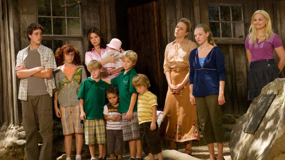 Henrickson wives and kids stand in front of cabin