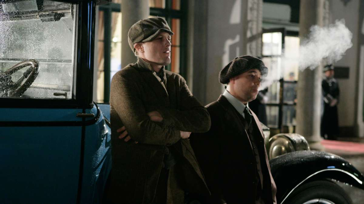 Jimmy Darmody and Al Capone lean against car