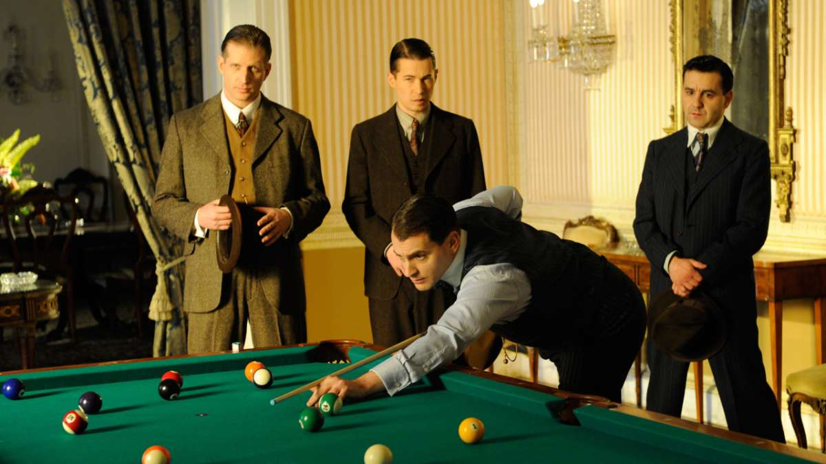 Rothstein playing pool surrounded by D'Alessios