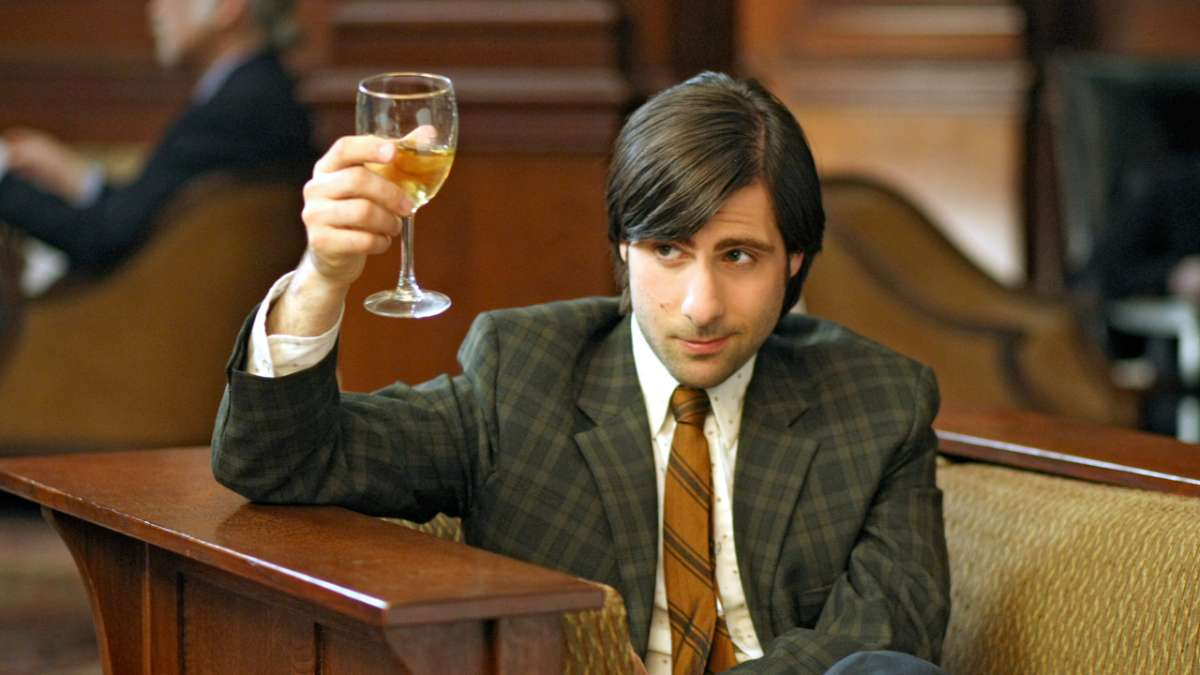 Jonathan Ames raises glass of white wine