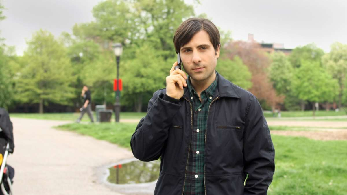 Jonathan Ames in park on cell phone