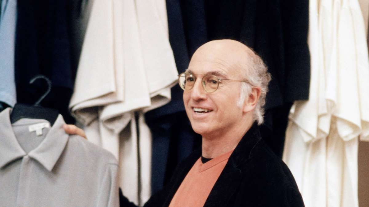 Larry David holding shirt on hanger