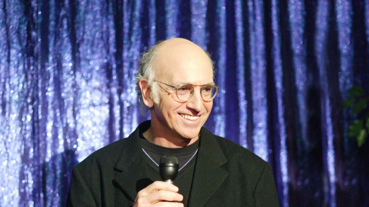 Larry David holds microphone on stage
