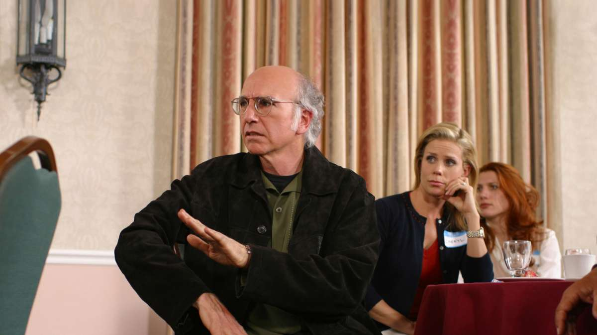 Larry David sits Cheryl sits behind at event