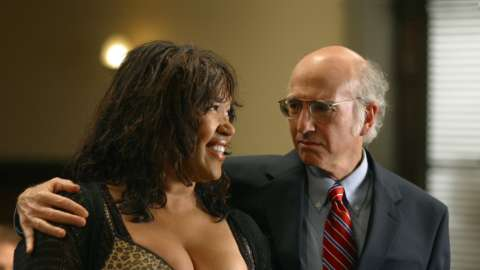 Larry David arm around looking at busty woman