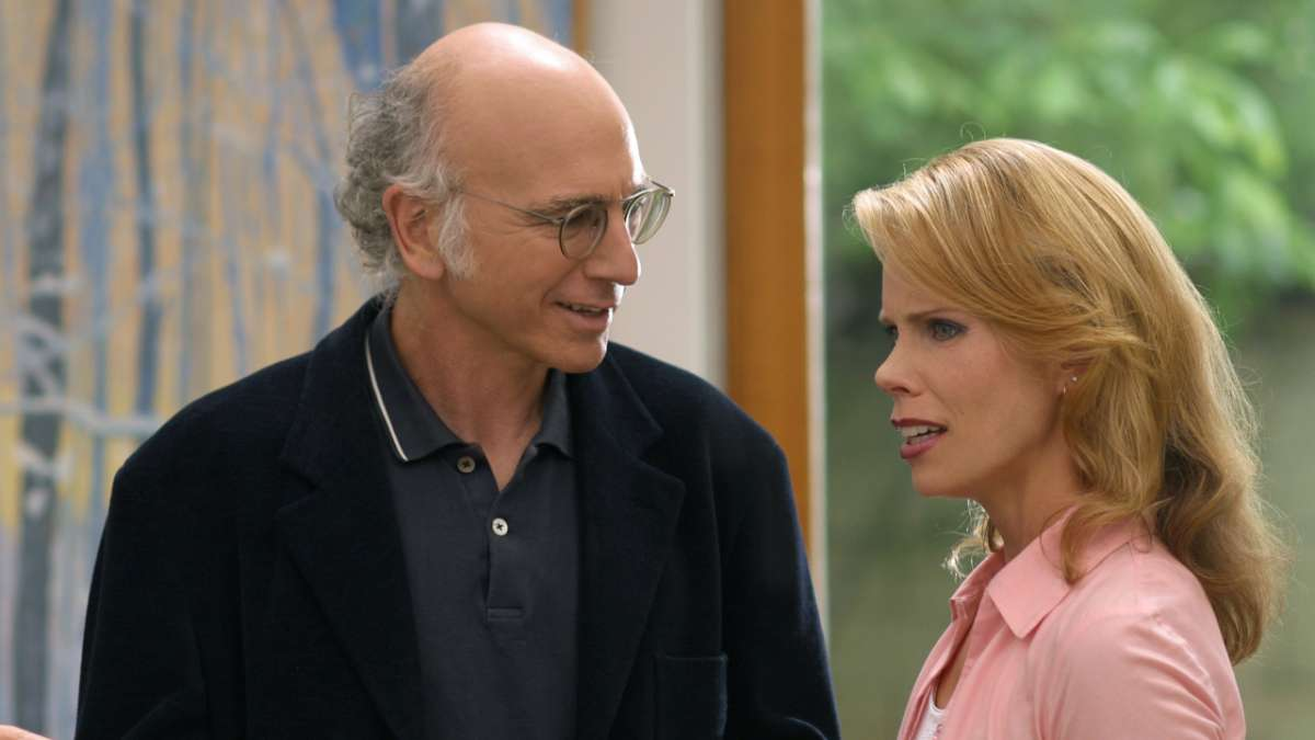 Larry David and Cheryl talking to each other by window