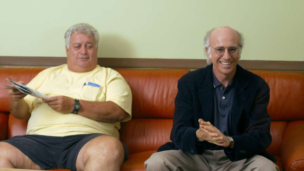 Overweight man with magazine and Larry David