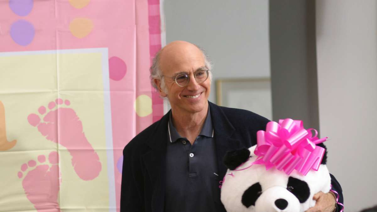 Larry David holds panda toy with pink bow