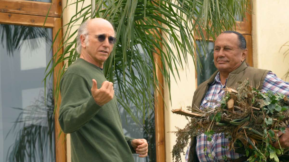 Larry David in sunglasses pointing Wandering Bear smiling