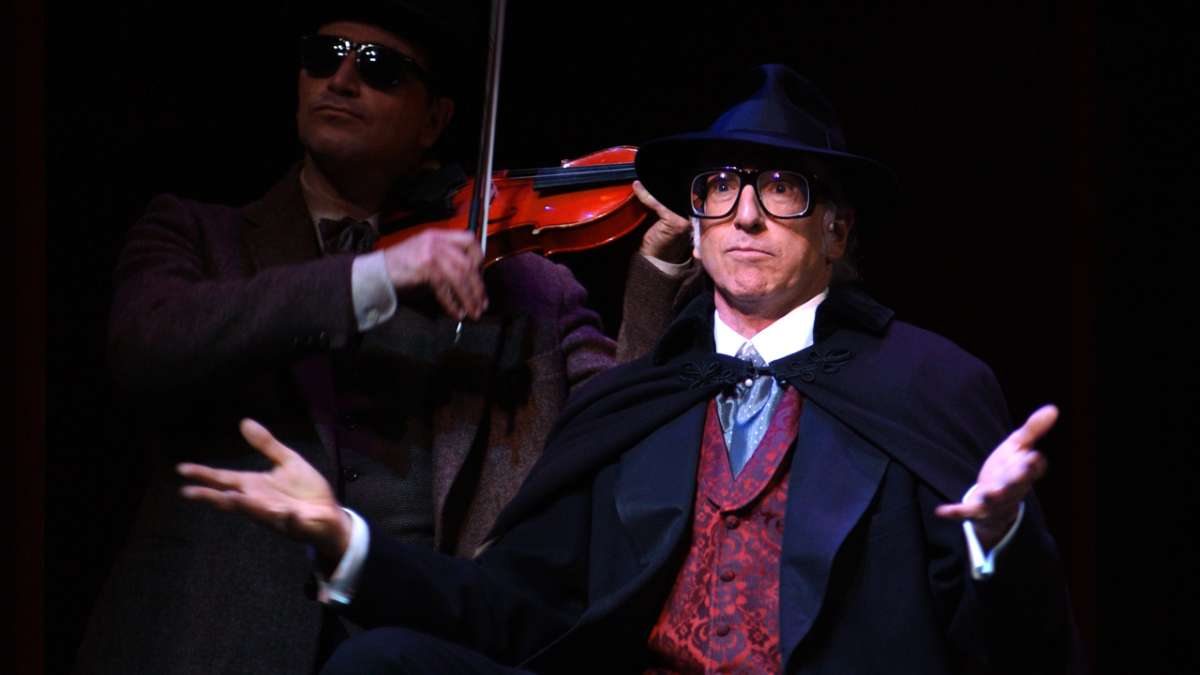 Larry David performing in The Producers shrugs with violinist behind