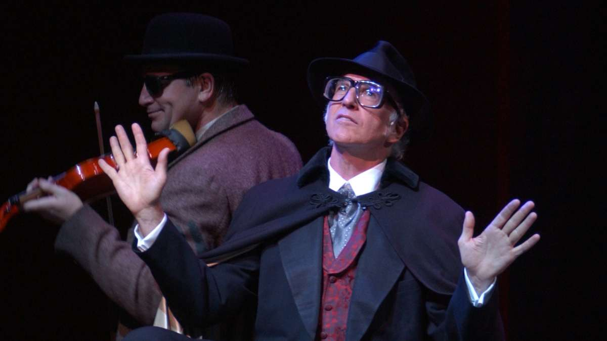 Larry David performing in The Producers looks up with violinist behind