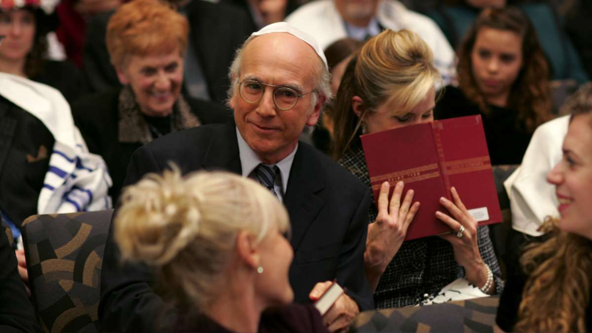 Larry David and Cheryl in temple audience laughing