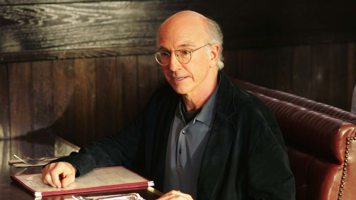 Larry David at restaurant booth with menu