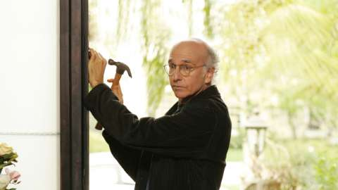 Larry David hammers nail into door frame