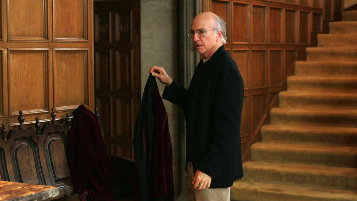 Larry David holds up smoking jacket near staircase Playboy mansion