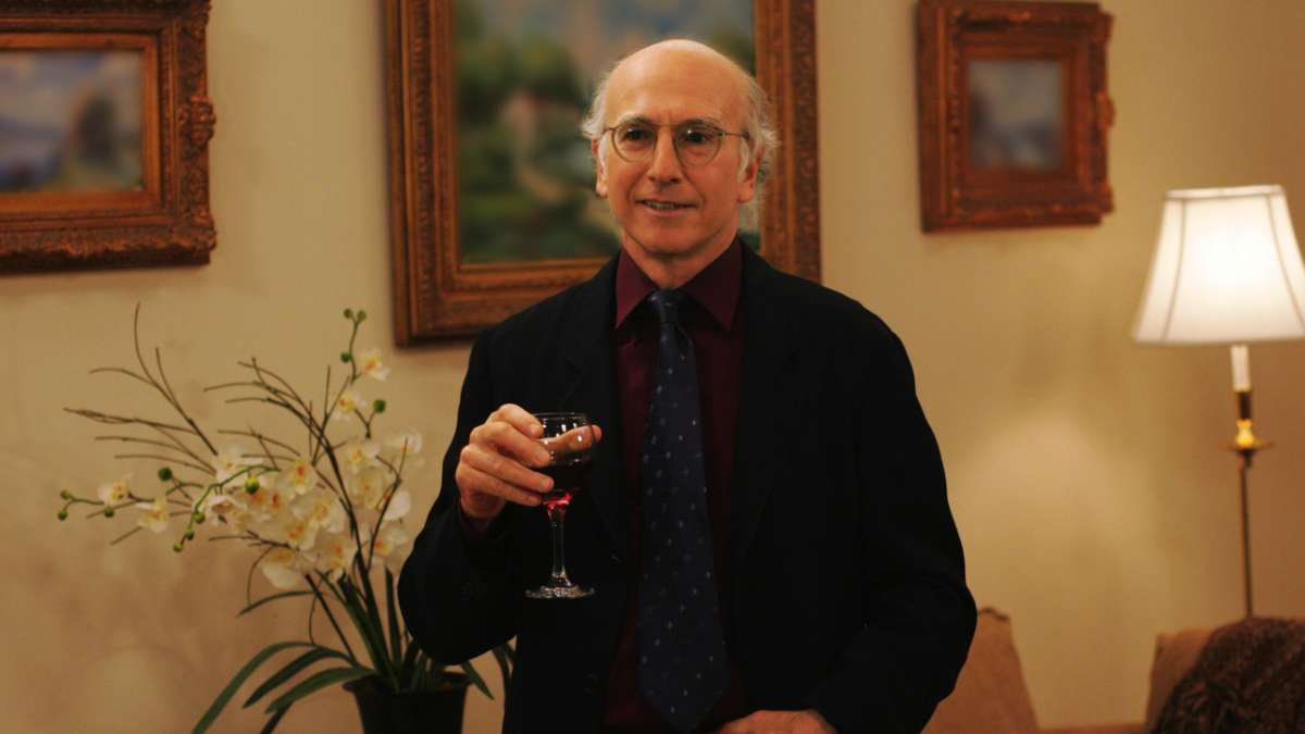 Larry David holding glass of red wine