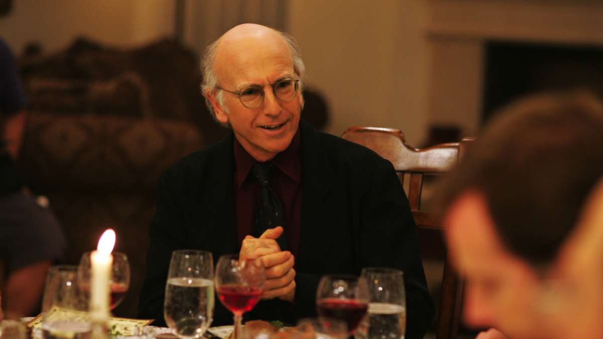 Larry David hands clasps at dinner table