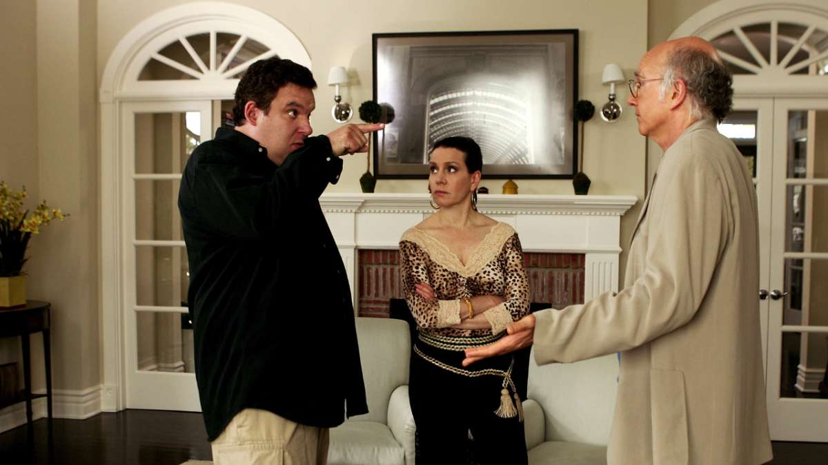 Jeff Greene pointing at Larry David in living room with Susie