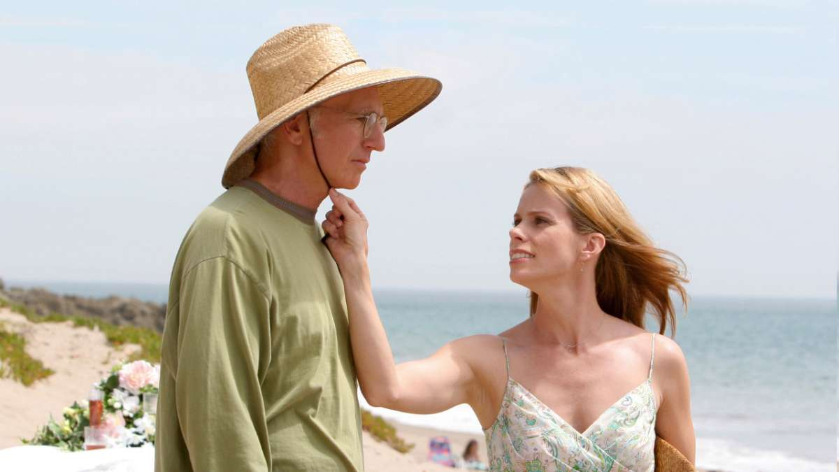 Cheryl and Larry David in straw hat on beach