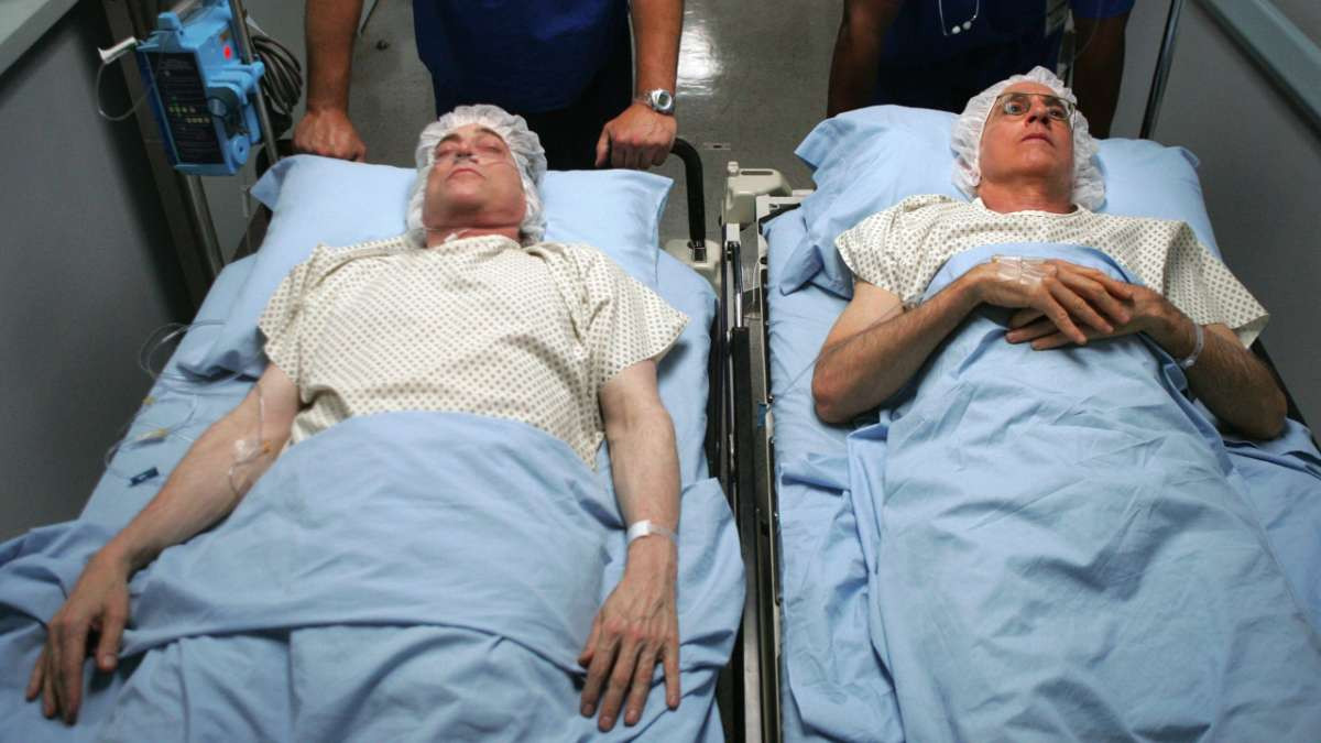 Richard Lewis and Larry David laying down on gurneys in hospital