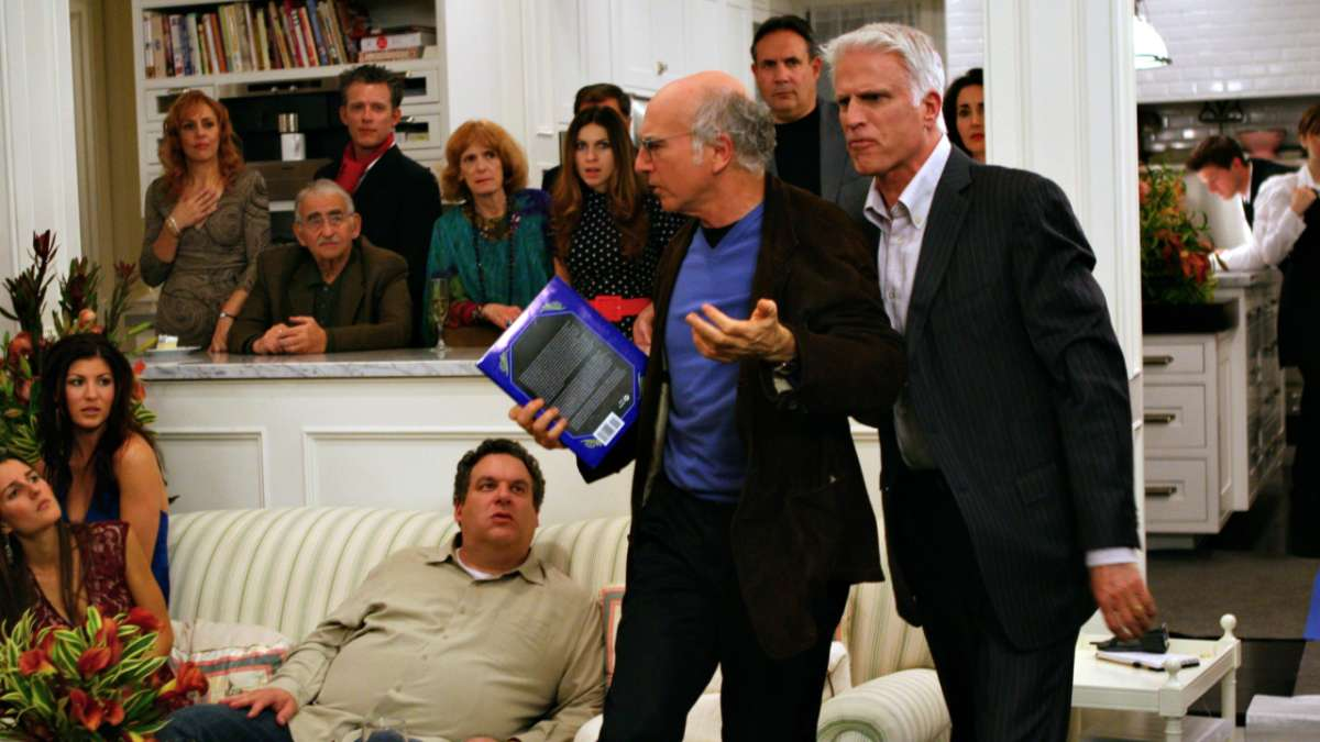 Larry David holding book at party with Ted Danson and Jeff Greene