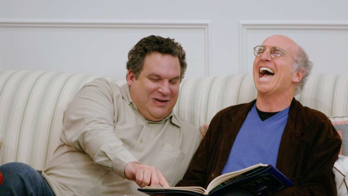 Jeff Greene points at book while Larry David laughs