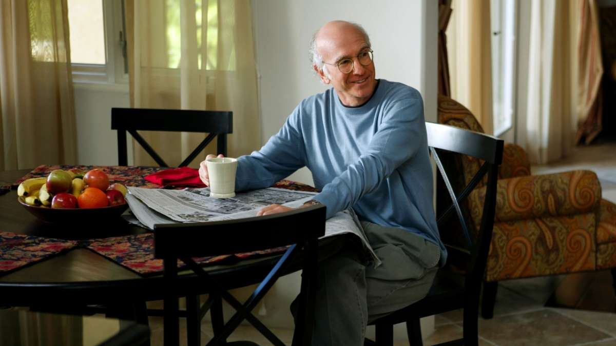 Larry David reading paper holding coffee mug