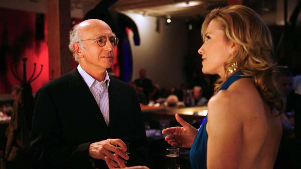 Larry David talking to woman in sexy dress