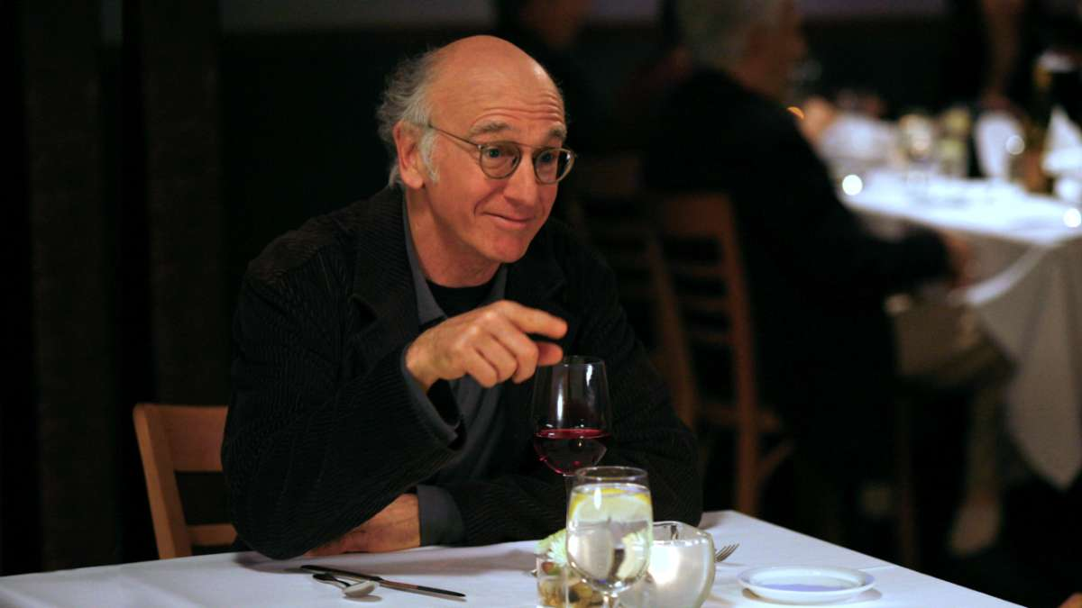 Larry David at restaurant table with wine pointing
