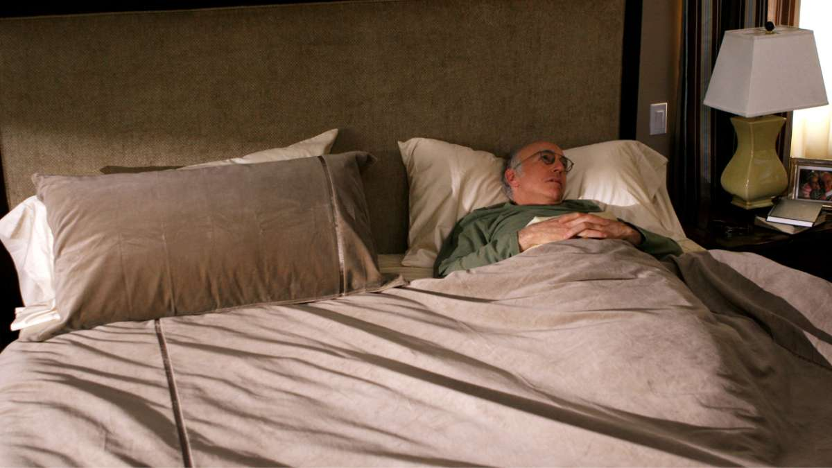 Larry David in bed alone