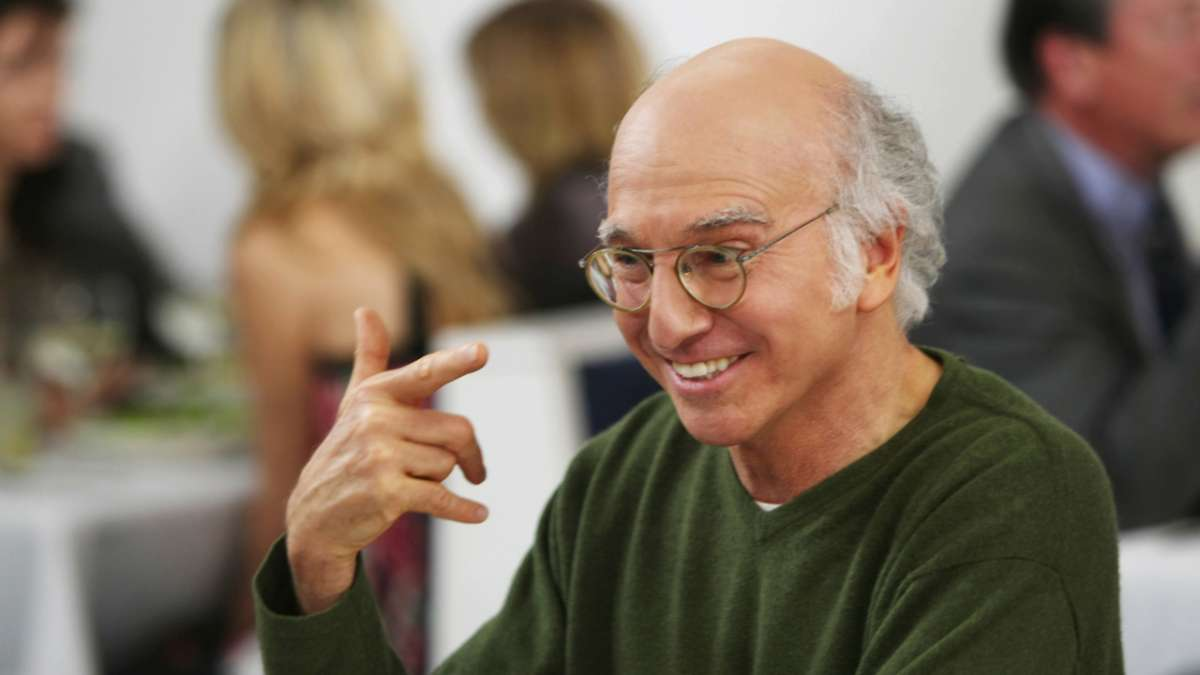 Larry David pointing at himself smiling