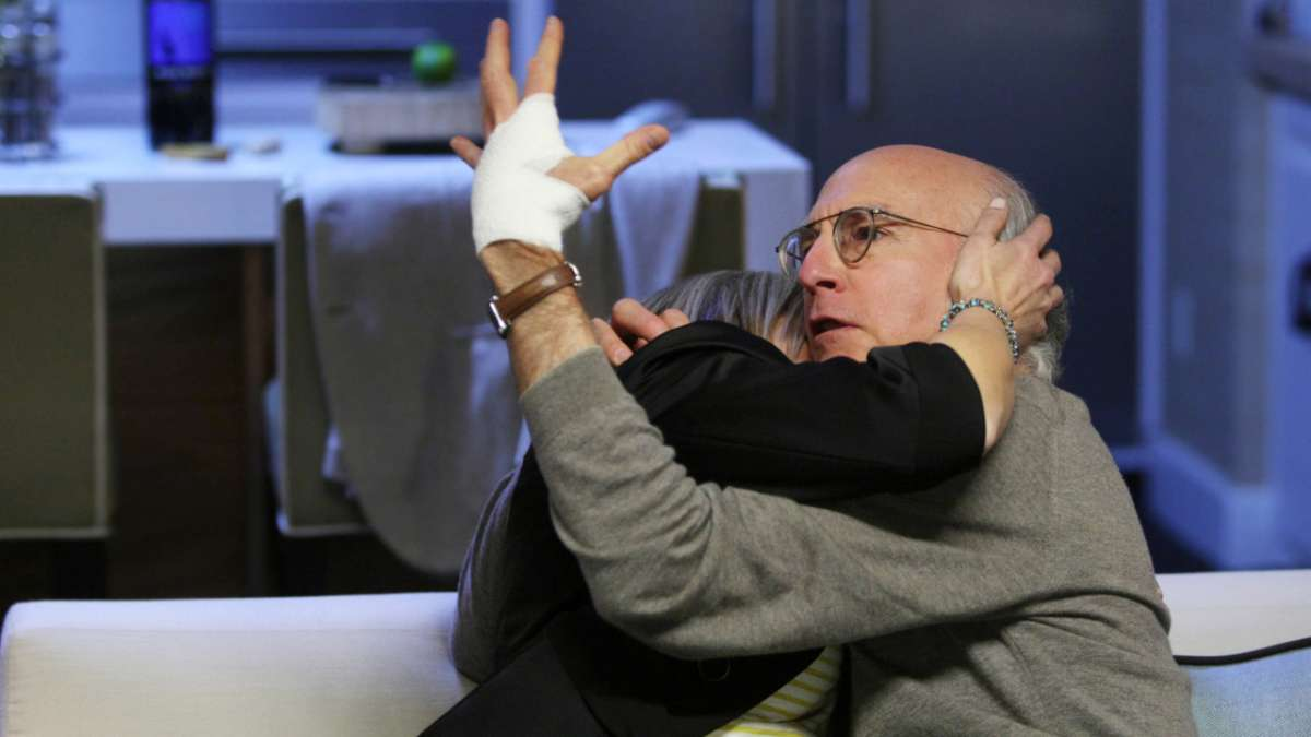 Larry David looks at bandaged hand while making out with woman