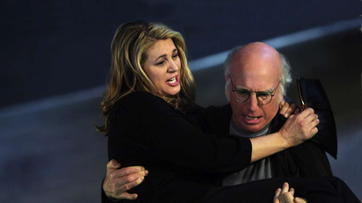 Larry David carrying handicapped woman up stairs
