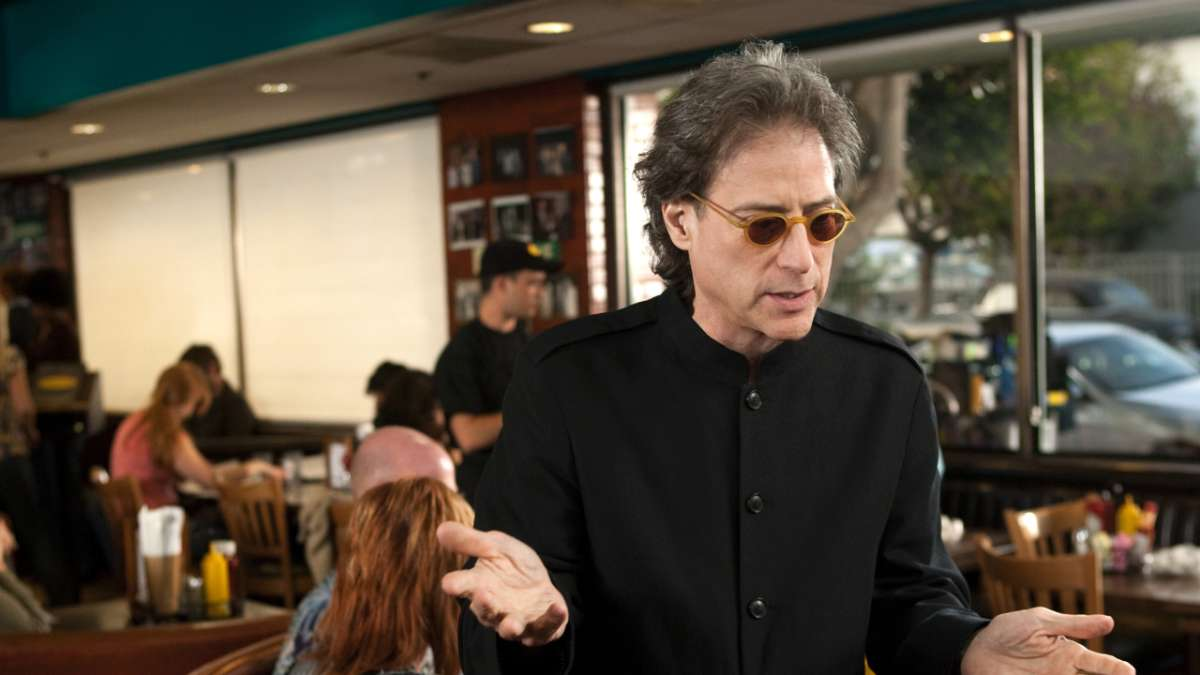 Richard Lewis in sunglasses in diner