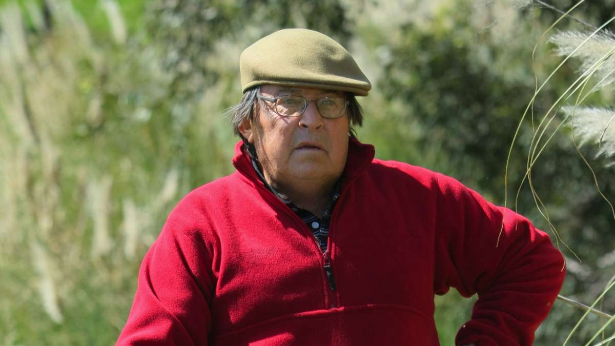 Golfer in red jacket and tan hat