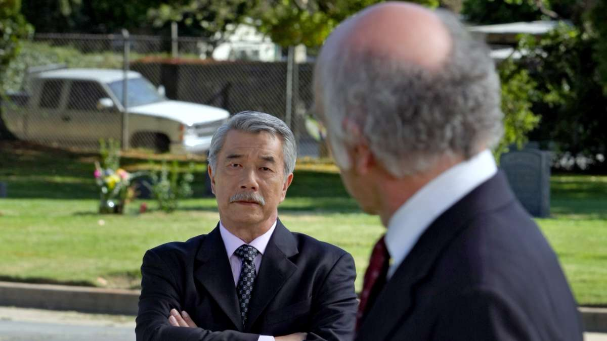 Middle aged Asian man stares at Larry David in cemetery
