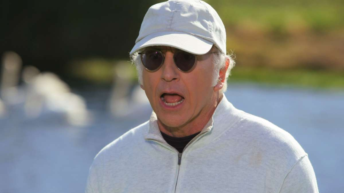 Larry David yelling in white cap